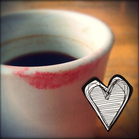 Close-up of white coffee mug with lipstick on the edge, sketch of heart in lower right corner